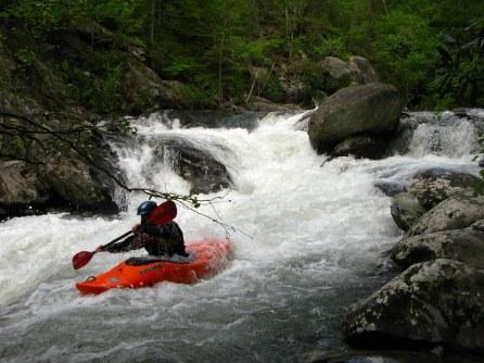 kayak going through rapids